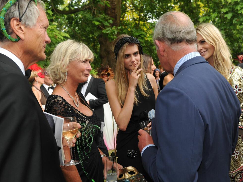 OPPFØRTE SEG: Cara (midten) så ut til å anstrenge seg for å beholde en sivilisert tone da hun og familien møtte prins Charles. Men stemningen ble altså svært munter etter hvert.  Foto: All Over Press