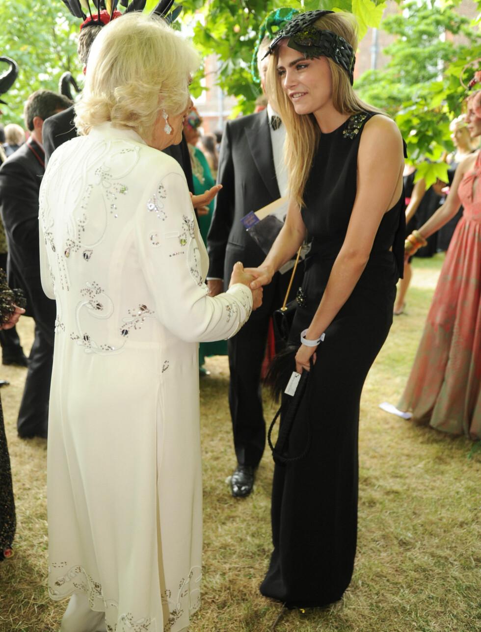SJARMERTE: Også hertuginne Camilla av Cornwall så ut til å sette pris på møtet med flotte Cara Delevingne.  Foto: All Over Press