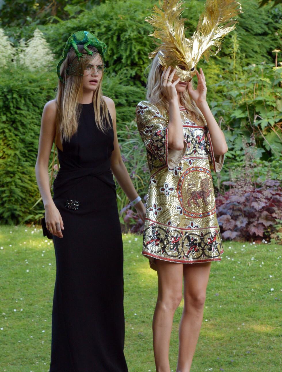 FLOTTE SØSTRE: Både Cara og Poppy Delevingne (t.h) tok seg svært godt ut i sine dyreinspirerte antrekk på festen på Clarence House i London.  Foto: All Over Press