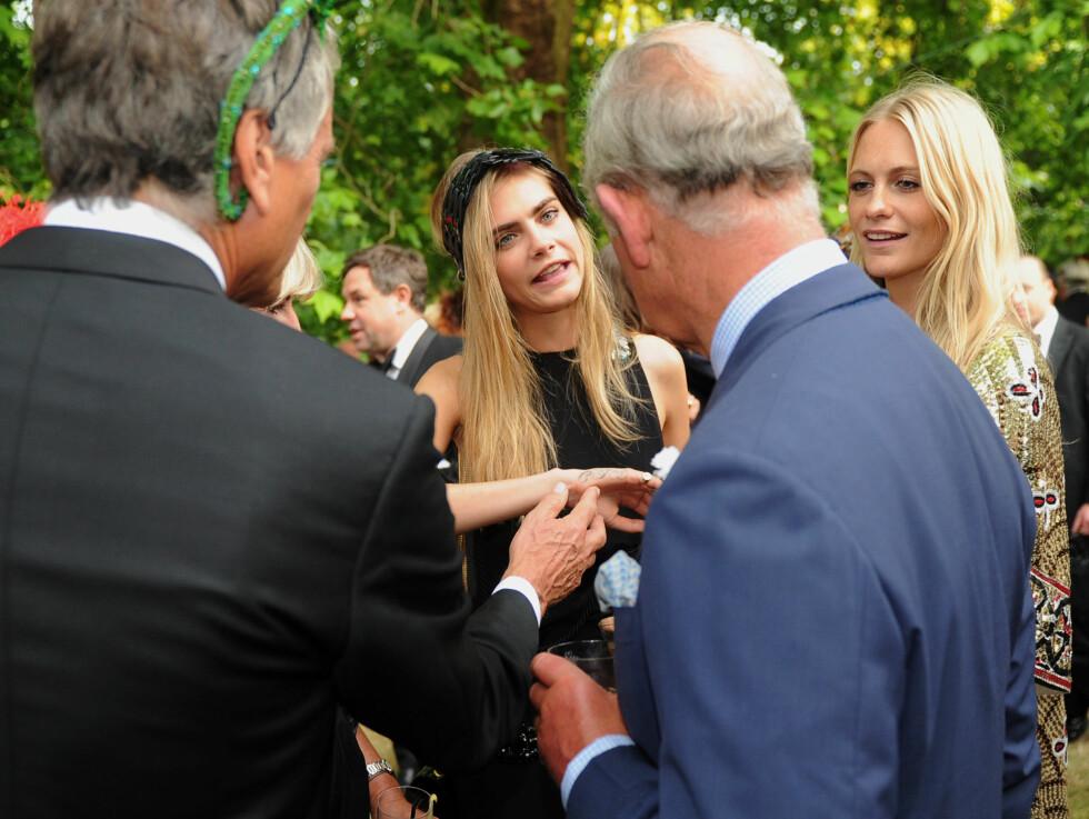 STOR INTERESSE: Hele Caras familie, deriblant søsteren Poppy (t.h), og selveste prins Charles diskuterte ivrig den unge toppmodellens mange tatoveringer. 20-åringen har flere tatoveringer bare på den ene hånden.   Foto: All Over Press