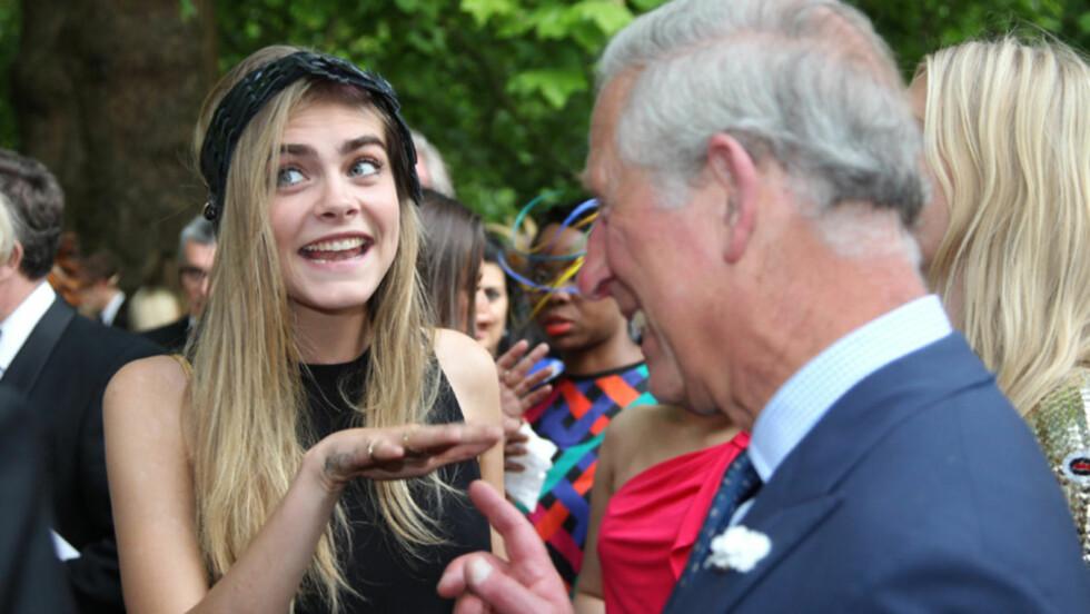 «TATTIS»-INTERESSERT: Toppmodell Cara Delevingne (t.v) viste gladelig frem tatoveringene sine til en interessert prins Charles i London tirsdag. Hun og modellsøsteren Poppy (t.h) var blant gjestene på en veldedighetsfest arrangert av prinsen og hans h Foto: Stella Pictures