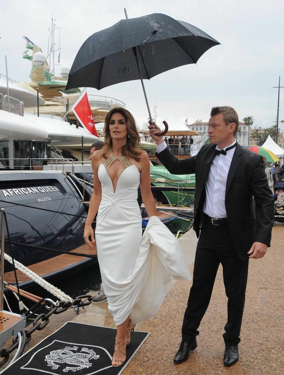 VÅT: Cindy Crawford koste seg på båten til Roberto Cavalli før åpningsfesten, men det så ikke ut til at hun satte spesielt stor pris på regnet som høljet ned. Heldigvis hadde hun en paraplybærer med seg... Foto: All Over Press