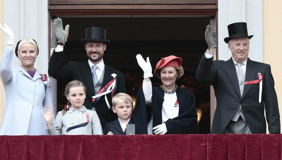 2012: Kronprins Haakon, prinsesse Ingrid Alexandra, kronprinsesse Mette Marit, prins Sverre Magnus, dronning Sonja og Kong Harald hilser på barnetoget utenfor Slottet. Foto: NTB scanpix