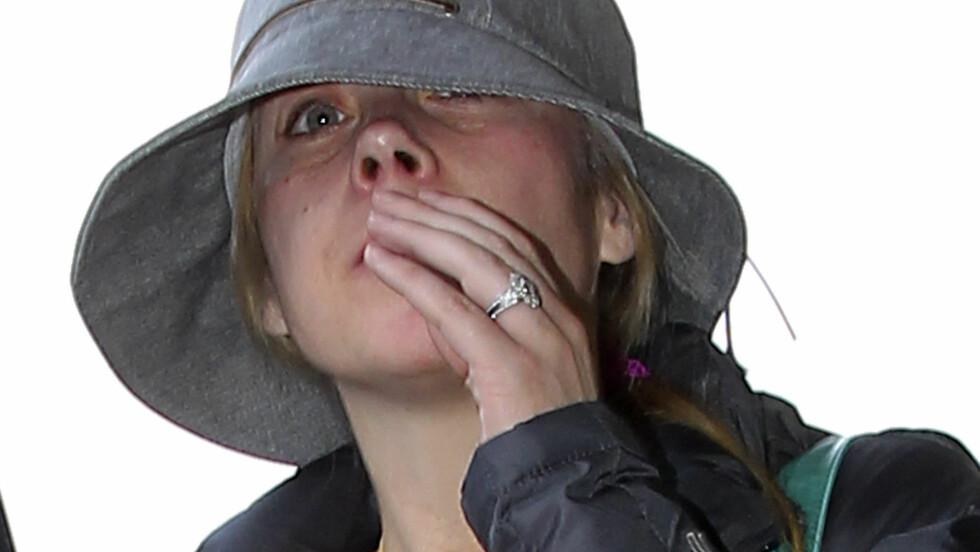 SKJULTE SEG: Christina Applegate prøvde å skjule seg da hun landet på flyplassen i Los Angeles, men ble raskt lagt merke til på grunn av den store forlovelsesringen.  Foto: FameFlynet
