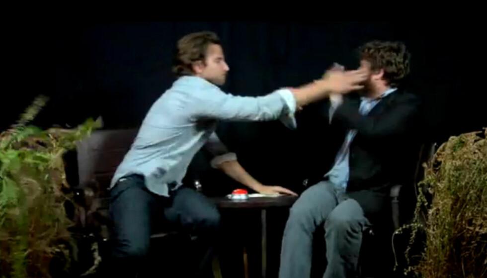 """FRA BLÅMANDAG TIL BLÅVEIS: Bradley Cooper mistet tilsynelatende fatningen og klappet til """"Hangover""""-kollegaen Zach Galifianakis under innspillingen av en sketsj. Foto: Funnyordie.com"""