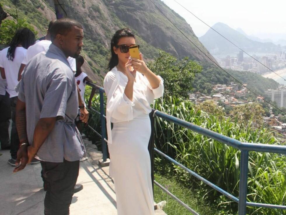BABYMAGE: Kim beskuer kjærestens bilde, og Kim viser fotografene i Rio babymagen i den tettsittende kjolen. Foto: All Over Press