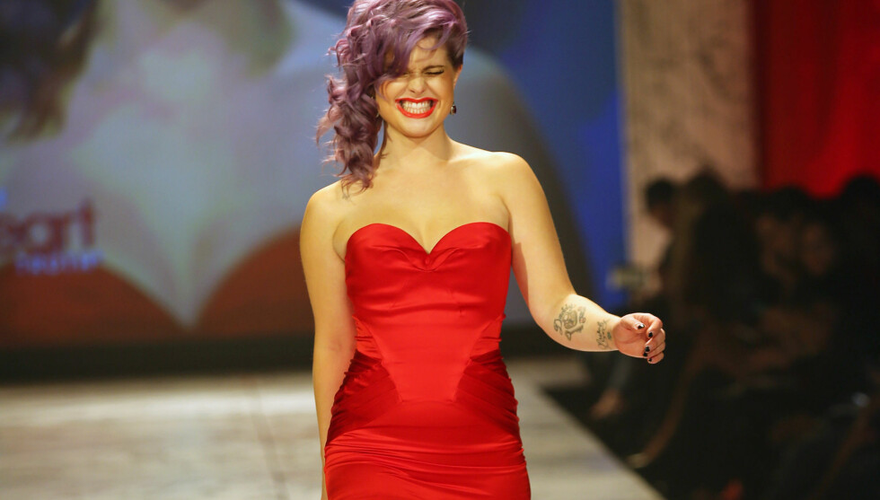 FORNØYD: Kelly Osbourne så ut til å storkose seg da hun viste formene i denne lekre Zac Posen-kjolen under The Heart Truths Red Dress Collection-moteshow i New York onsdag.  Foto: All Over Press