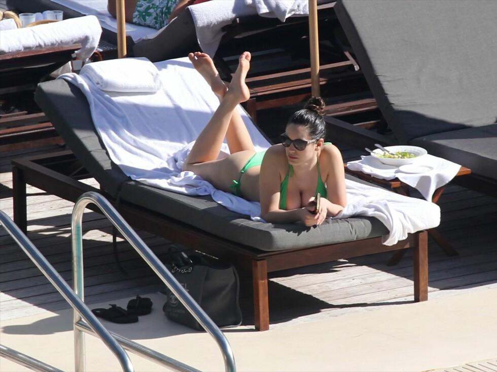 ALENE: Den nysingle modellen virket ikke særlig fornøyd med å ligge ensom ved svømmebassenget i Miami Beach.  Foto: All Over Press