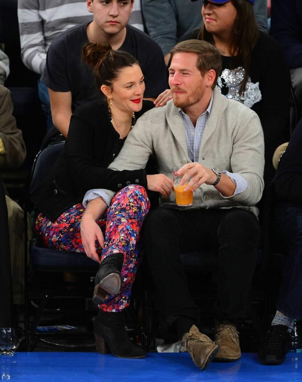 FORELSKA: Drew Barrymore og ektemannen Will Kopelman giftet seg i fjor, og er opp etter ørene forelska. I forrige uke hadde de to fått skaffet barnevakt til lille Olive, og koste seg på basketballkamp i Madison Square Garden i New York. Foto: All Over Press