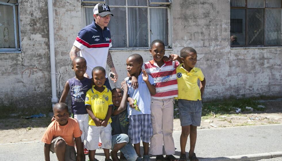KOSTE SEG MED BARNA: Bjørn Helge og resten av landslaget fikk en guidet tur til byen Guguletu som er et av de fattigste bo områdene utenfor Cape Town.  Foto: NTB scanpix
