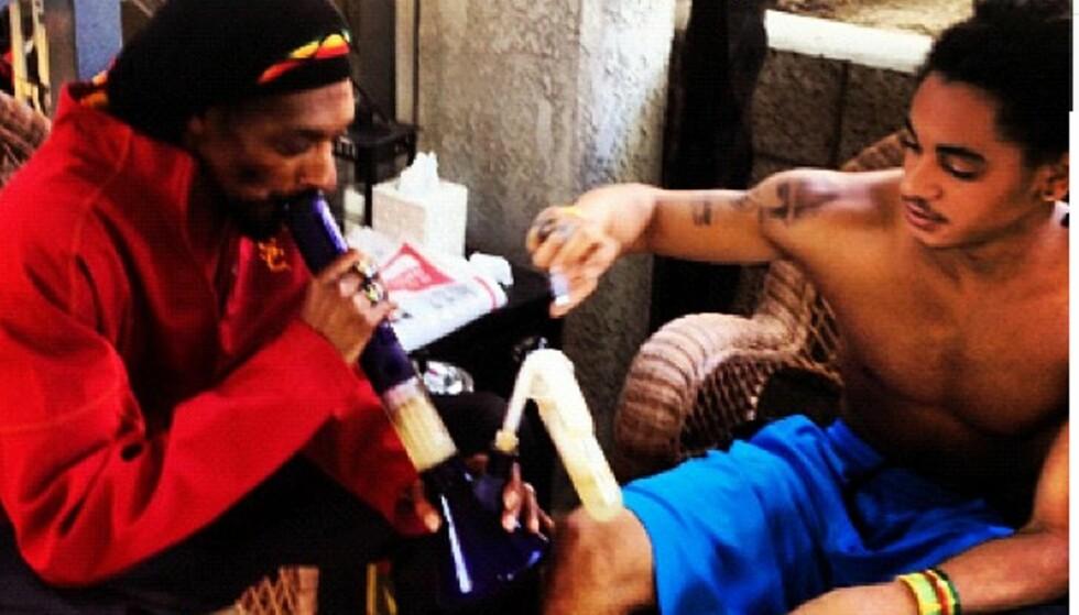 VISER SØNNEN: Hva slags stoff som røykes gjennom denne bongpipen er uvisst, men Snoop virker å lære sønnen Corde noen triks. Foto: All Over Press