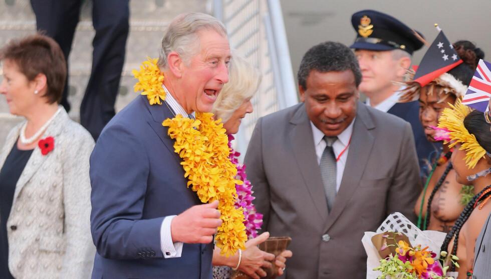 OVERRASKET: Prins Charles fikk seg en overraskelse på flyplassen i Port Moresby på Papua Ny-Guinea, da han ble møtt av toppløse dansere.  Foto: All Over Press