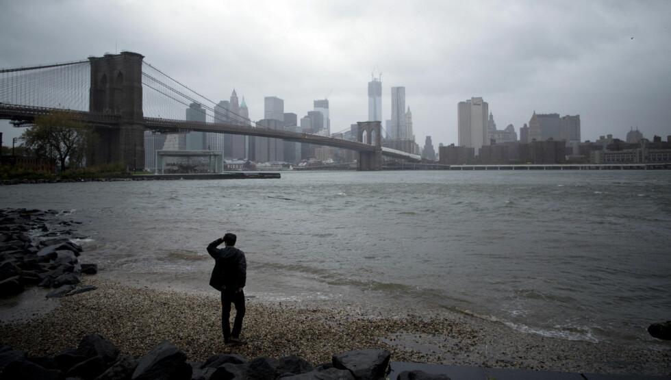 STILLE FØR STORMEN: En mann titter over på Manhattan Skyline fra Brooklyn, i det orkanen bygger seg opp. Sterk vind og mye nedbør i løpet av dagen har gitt New Yorkerne en pekepinn på hva de har i vente når Sandy treffer land.  Foto: Reuters