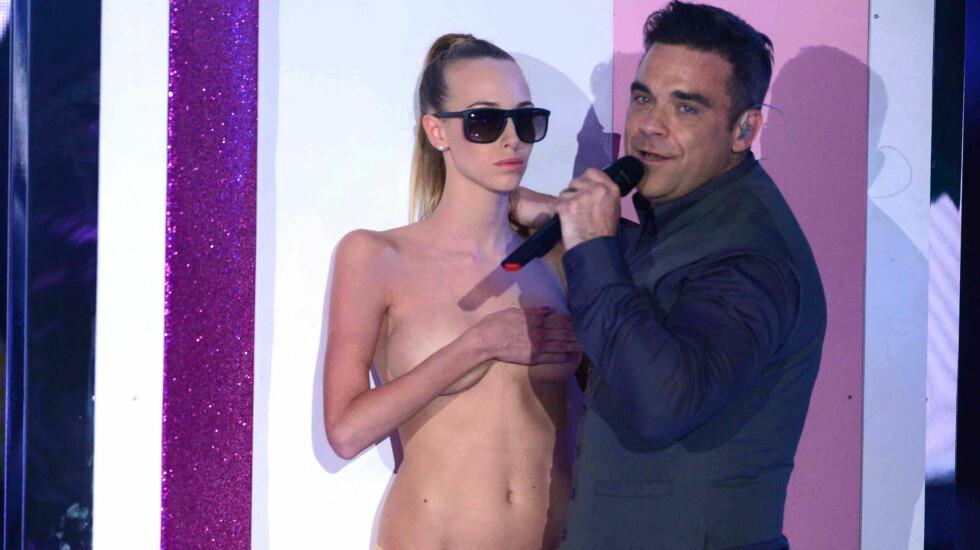 FREKK OPPTREDEN: Robbie Williams koste seg på scenen i Italia da han danset sammen med en rekke toppløse modeller, kun iført små stringtruser.  Foto: Fame Flynet
