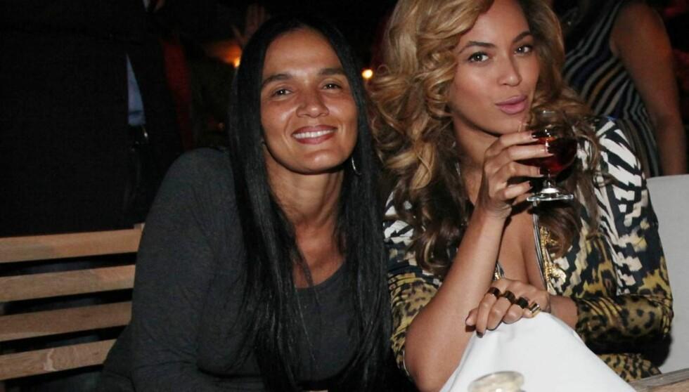 SKJULER MAGEN: Beyoncé poserte sammen med ektemannens forretningspartner Desiree Perez under cocktailfesten søndag kveld. Hun plasserte en serviett strategisk foran magen, og latet som hun sippet til cognacen for fotografene.  Foto: All Over Press