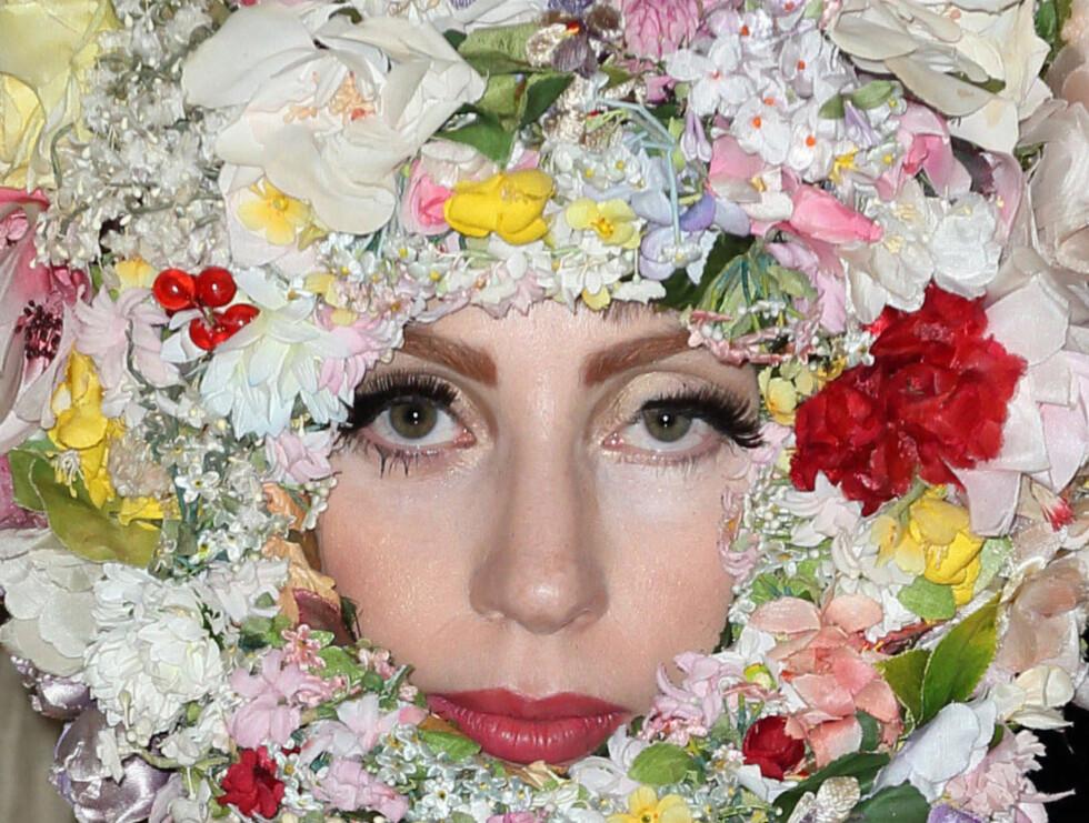 BLOMSTERPIKE: Popstjernen Lady Gaga sparte ikke på noe da hun gjestet moteshowet til hattedesigner Philip Treacy under LOndon Fashion Week søndag. Hun ankom visningen i en kreasjon som minnet om en motorsykkelhjelm druknet i falske blomster.  Foto: All Over Press