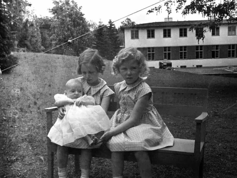 1937:  Prinsesse Ragnhild  (tv) og prinsesse Astrid med prins Harald, ca seks måneder gammel. De tre sammen, sittende på en benk i hagen.   Foto: SCANPIX