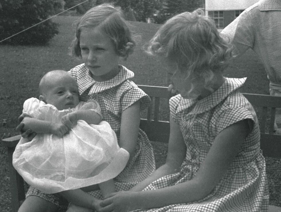 SKAUGUM 1937: Prinsesse Ragnhild  (tv) og prinsesse Astrid med prins Harald, her ca fire måneder gammel. De tre sammen, sittende på en benk i hagen.  Foto: SCANPIX