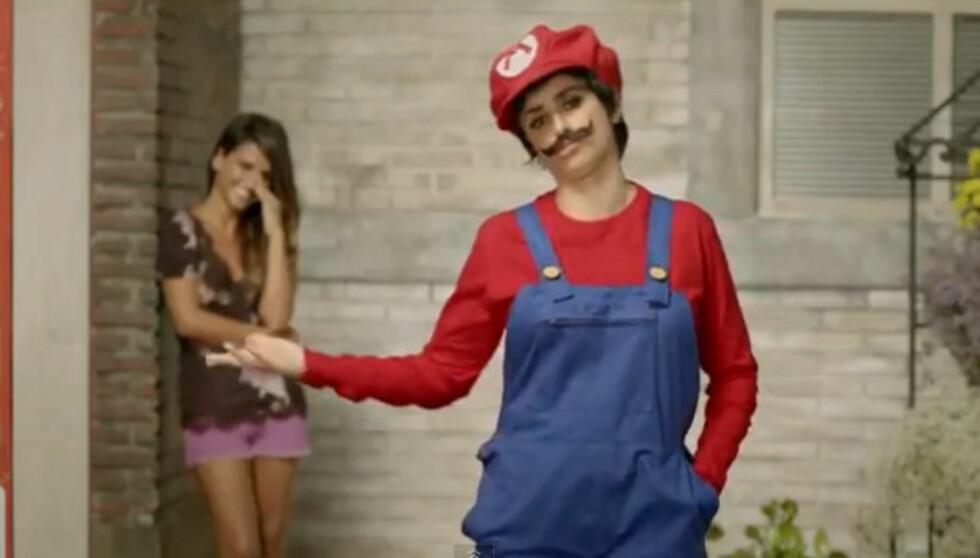 I KOSTYME: Reklamefilmen ender med at skjønnheten viser seg fram i Mario-kostyme, mens søsteren Monica står i bakgrunnen og ler. Foto: YouTube