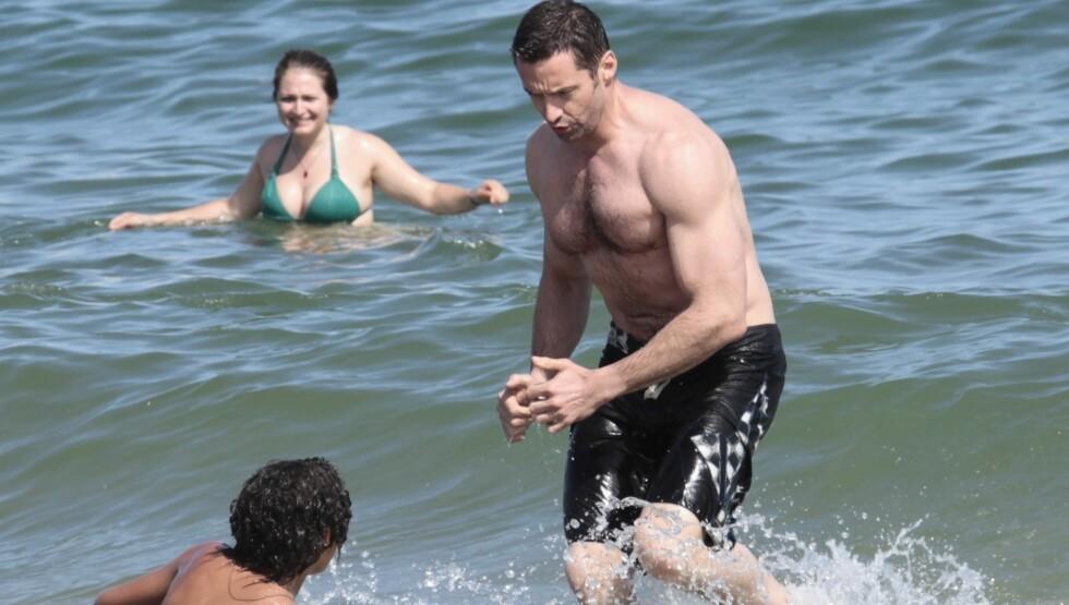SÅNN SER HAN EGENTLIG UT: Hugh på badeferie med kona og barna tidligere i sommer. Før han la seg i hardtrening til den nye rollen. Foto: Fame Flynet