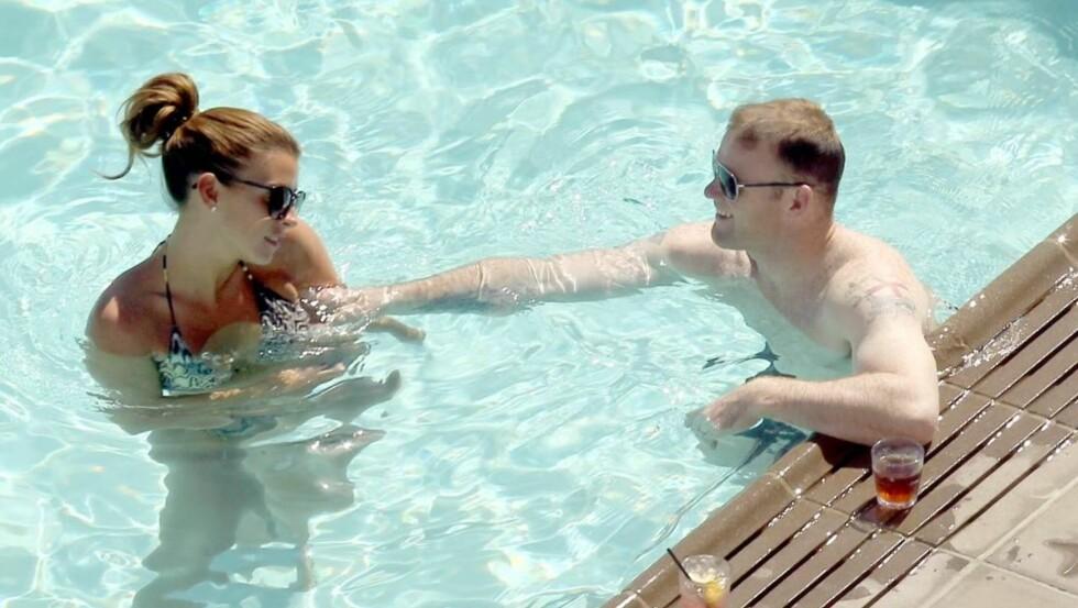 COME ON, COLEEN: Wayne Rooney kunne ikke dy seg for å spøke og flørte litt med sin kone i bassenget i Los Angeles. Foto: All Over Press