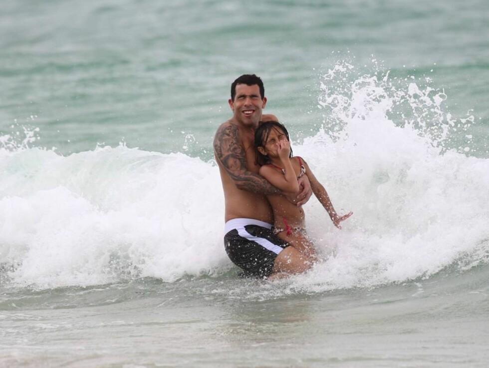 SE, HAN SMILER!: Carlos Tevez storkoste seg i bølgene med sin eldste datter. Foto: All Over Press