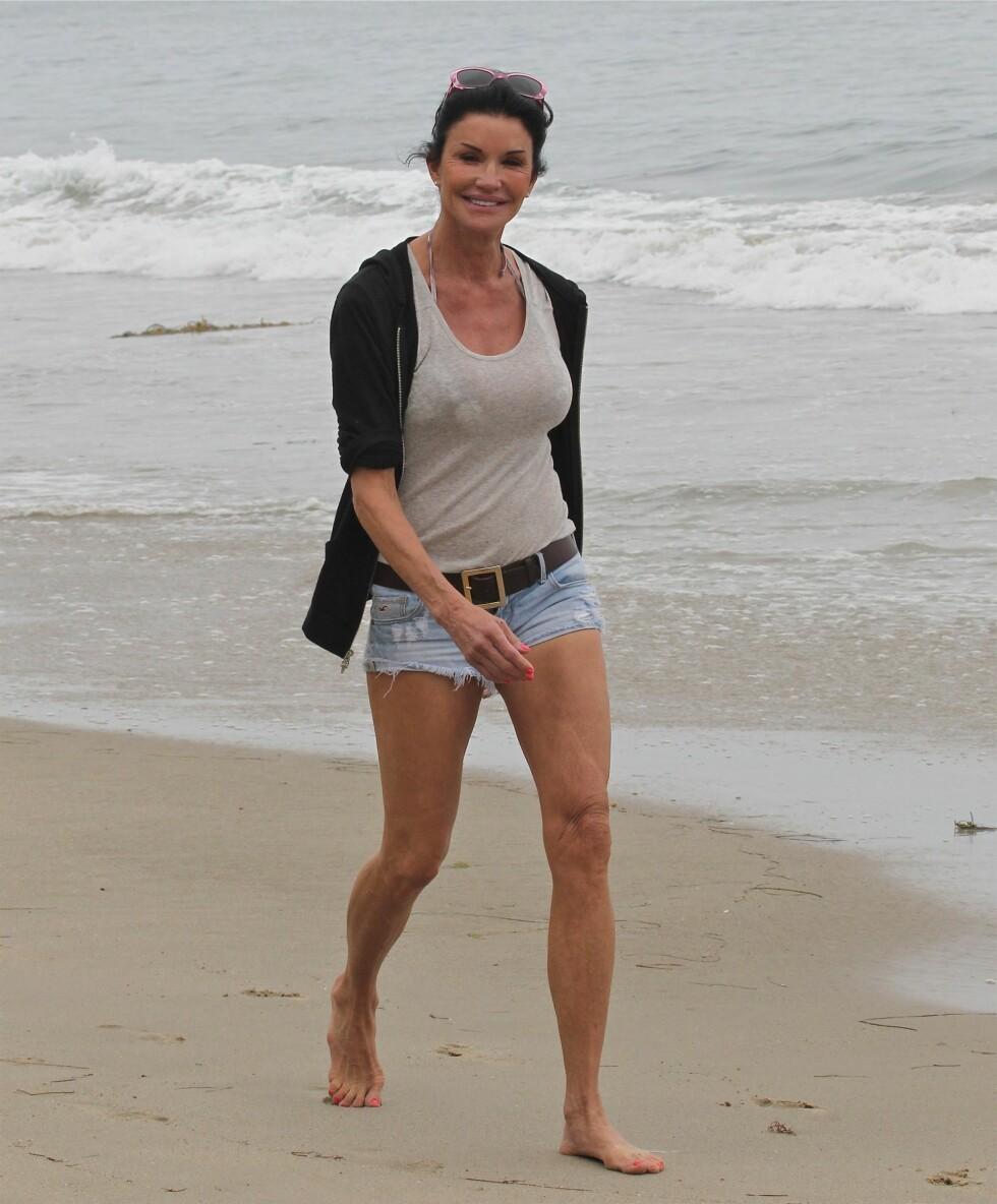SLAPPET AV: Men Janice Dickinson unnet seg også en deilig spasertur på stranden på den amerikanske nasjonaldagen. Hun viste villig sine veltrente ben for fotografene.  Foto: All Over Press