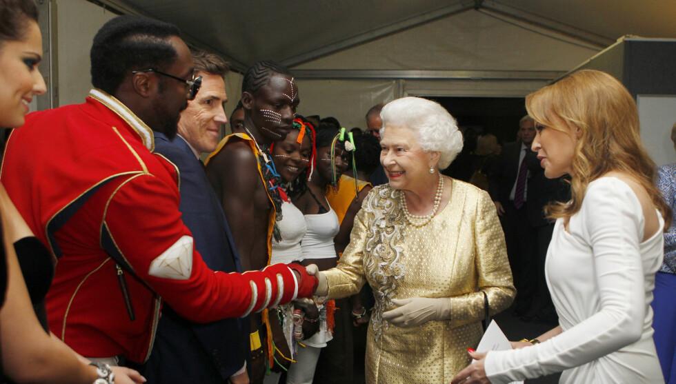 INGEN VONDE FØLELSER: Dronningen hilste høfflig på Will.I.Am bak scenen. Vel uvitende om at han klødde i Twitter-fingeren på scenen. Foto: Fame Flynet