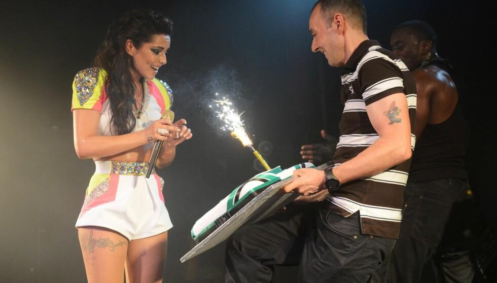 KAKE: Da hun hadde tømt glasset kom kaka. Cheryl feiret sin nye slager på hitlistene. Foto: All Over Press
