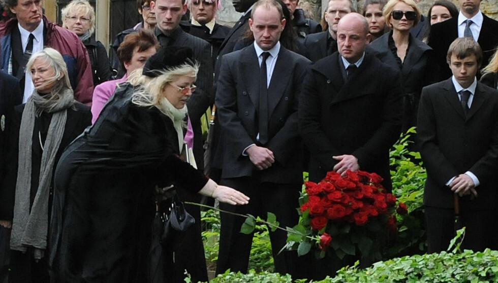 KASTET ROSE PÅ KISTA: Dwina Murphy Gibb kastet en rød rose på kisten til sin kjære mann under begravelsen på fredag.  Foto: All Over Press