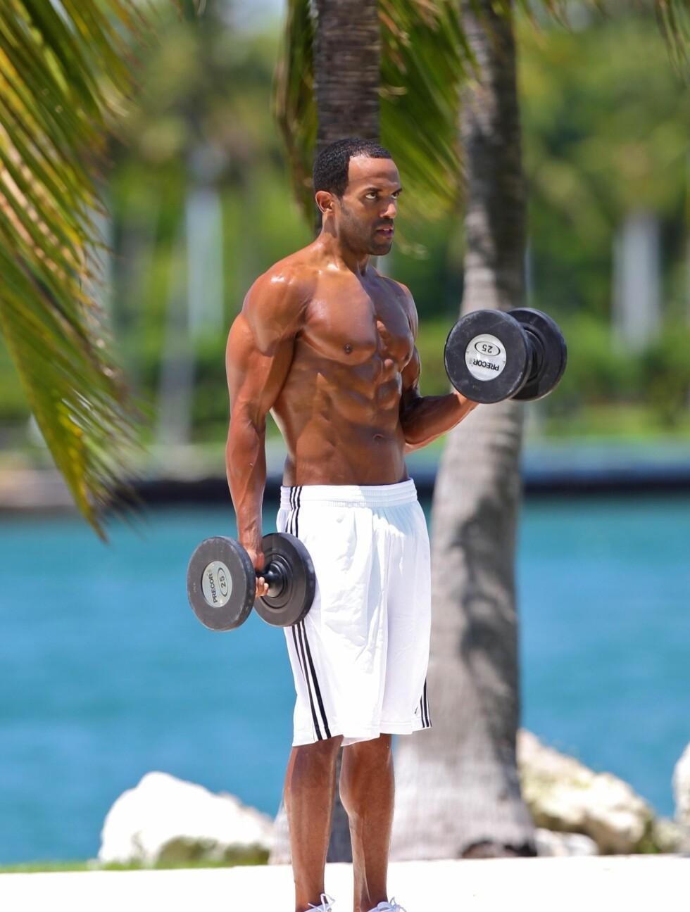 BICEPSCURL: Her ser vi Craig avsluttet treningsøkten med curl for bicepsen på overarmene. Hver manual har tallet 25 på. Sannsynligvis er det snakk om kilo. Foto: All Over Press