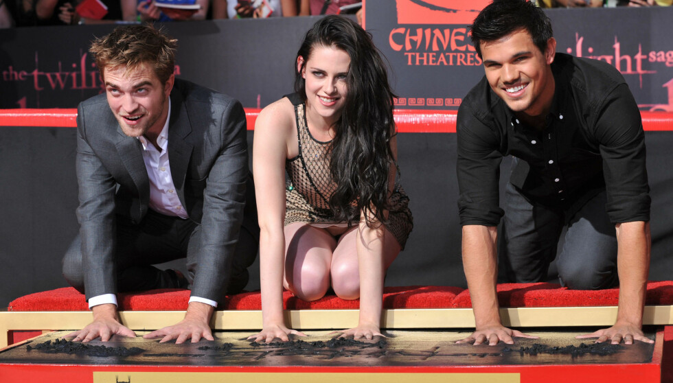 TRYKKET NED: De tre hovedrolleinnehaverne fra Twilight, Robert Pattinson (26), Kristen Stewart (22) og Taylor Lautner (20). Her avgir de sine håndavtrykk til Graumans kino i Los Angeles.  Foto: Fame Flynet