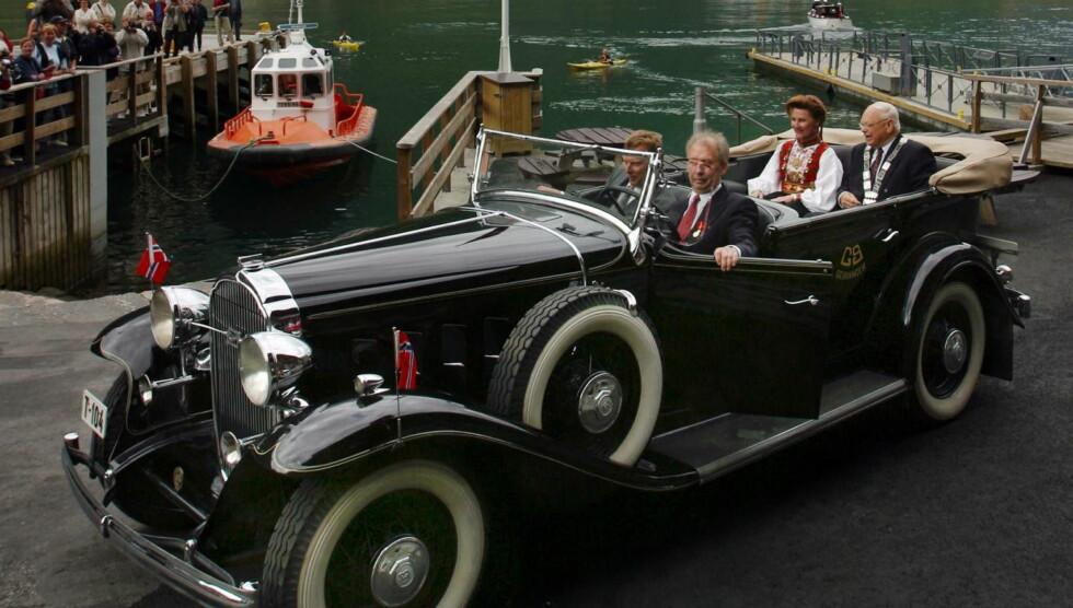 PRIVATSJÅFØR: Karl Mjelva har tidligere kjørt både kong Harald og dronning Sonja i en av sine mange veteranbiler. Her er han sjåfør da Sonja åpnet Fjordsenteret i Geiranger i 2002.  Foto: NTB scanpix