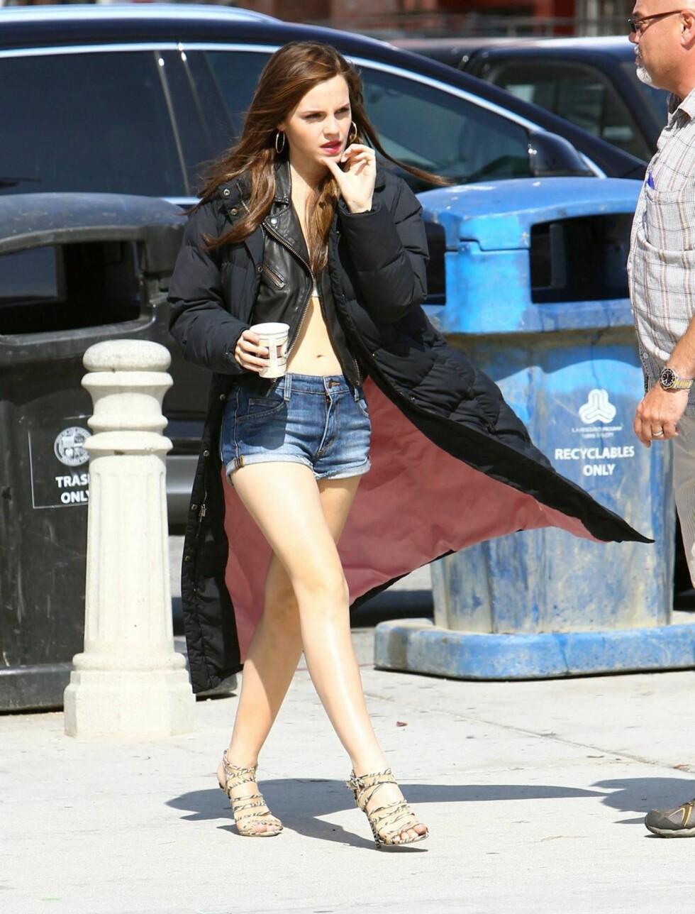 FORTRYLLENDE: «Harry Potter»-stjernen Emma Watson lar ikke litt vind hindre henne i å bruke favoritt-shortsen. Da tar hun bare på seg en lang frakk. Foto: Stella Pictures