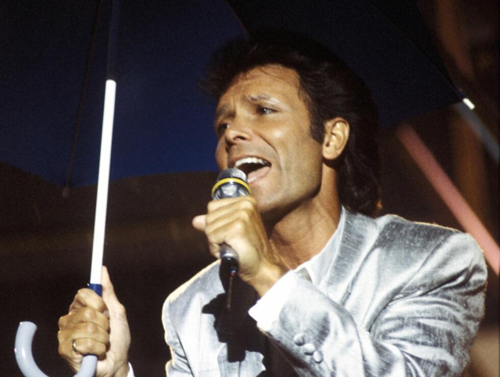 SINGING IN THE RAIN: Cliff Richard synger med paraply i regnværet under  Momarked-showet 1985.  Foto: NTB scanpix