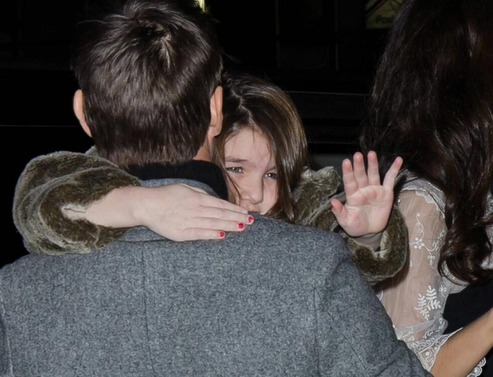 <strong>HILSER:</strong> Her vinker Cruises datter til pressen mens hun blir båret av faren.  Foto: All Over Press