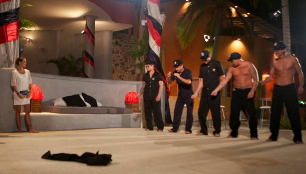 OVERRASKET TRIANA: Stian Thorbjørnsen (nr fire fra venstre) overrasket Triana Iglesias med å kle seg helt naken under tirsdagens «Mr. Paradise»-konkurranse. Foto: TV3