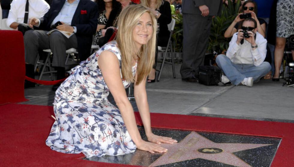 <strong>NED PÅ KNE:</strong> Slik så det ut da Jennifer Aniston tidligere i februar ble hedret med sin egen stjerne på Hollywoods Walk of Fame. Foto: Fame Flynet