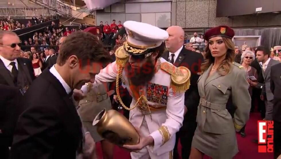 <strong>DIKTATORASKE:</strong> Sacha Baron Cohen kom til Oscar-utdelingen utkledd som sin nye karakter «The Dictator» og sølte Kim Jong-ils aske utover reporter Ryan Seacrest.  Foto: E! Online