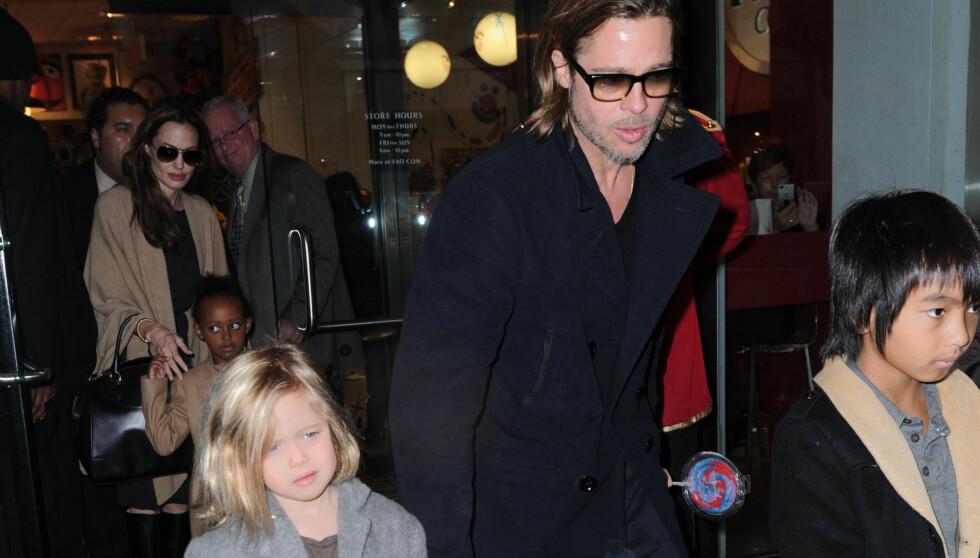 DATTER OG FAR: Her forlater Brad og Shiloh et hotell sammen i desember. Enda nyere bilder viser at datteren har mye kortere og mørkere hår. Foto: All Over Press