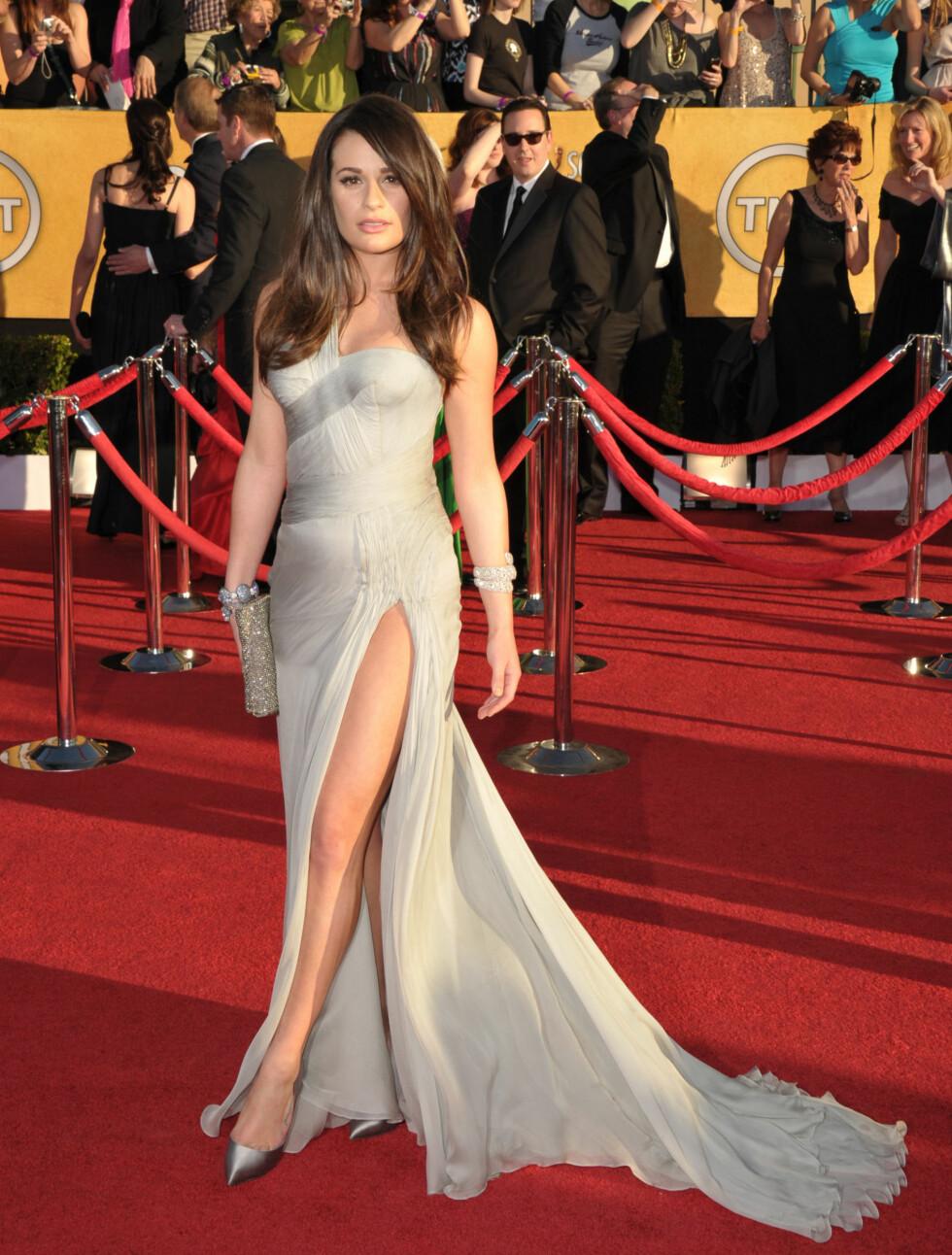 """GRESK GUDINNE: """"Glee""""-stjernen Lea Michele (25) lot sine lange bein komme til syne i denne elegante og sexy kjolen fra Versace. Skoene fra Casadei og clutchen fra Fendi komplimenterer kjolens sølvtoner perfekt.  Foto: All Over Press"""