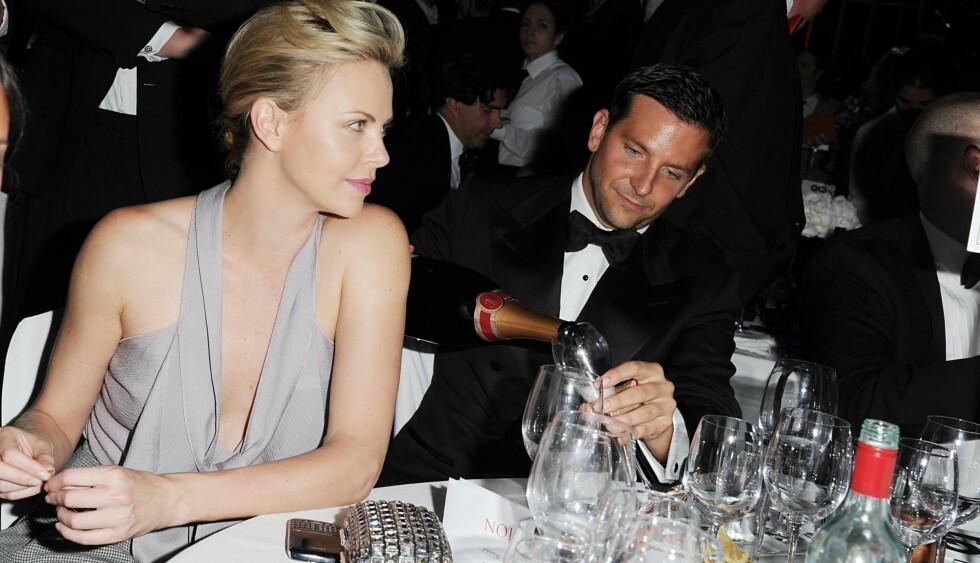 GENTLEMAN?: Bradley Cooper påstår at han har sluttet å drikke alkohol. Gentleman som han er heller han kanskje champagne i et glass til skuespillerkollega Charlize Theron, da de to gjestet «the GQ Men of the Year 2011 afterparty» i London i fjor høs Foto: Stella Pictures