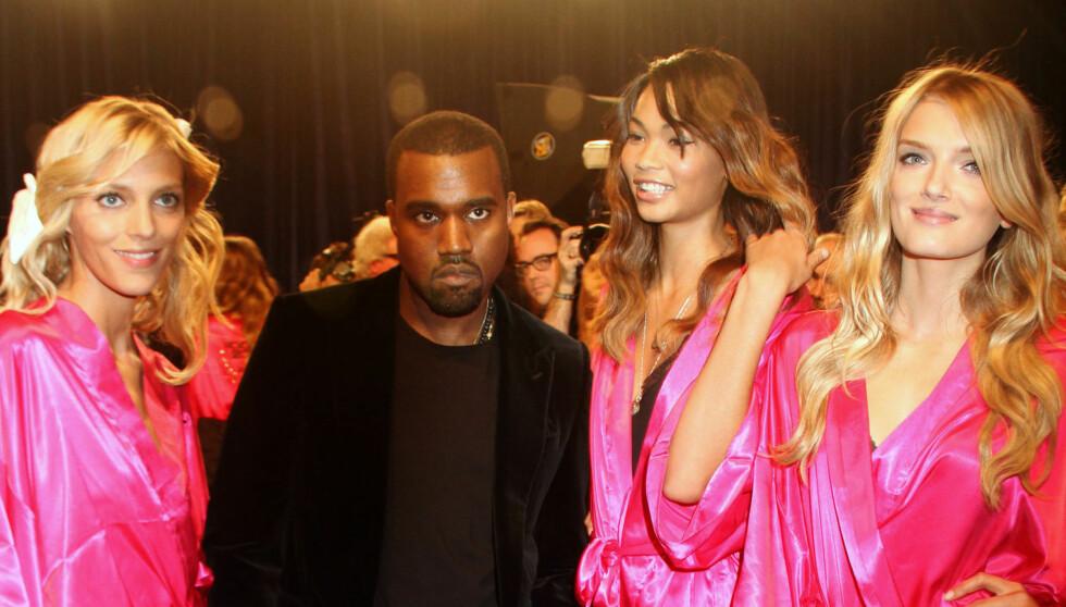 MODELLER: Kanye West leter etter modeller som kan gå show for ham, når kolleksjonen hans blir å se under Paris Fashion Week 2012. Her er han omringet av Victorias Secret-modeller. Foto: Stella Pictures