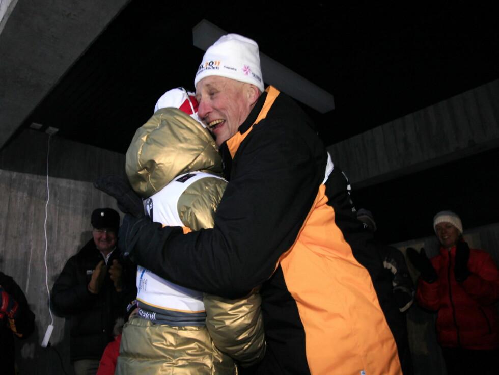 KONGEN FIKK KLEM AV SKIDRONNINGEN: Sportsinteresserte kong Harald fikk mange grunner til å juble da de norske utøverene håvet inn flere gull under ski-VM på hjemmebane i februar. Her får han en klem av Marit Bjørgen. Foto: Scanpix