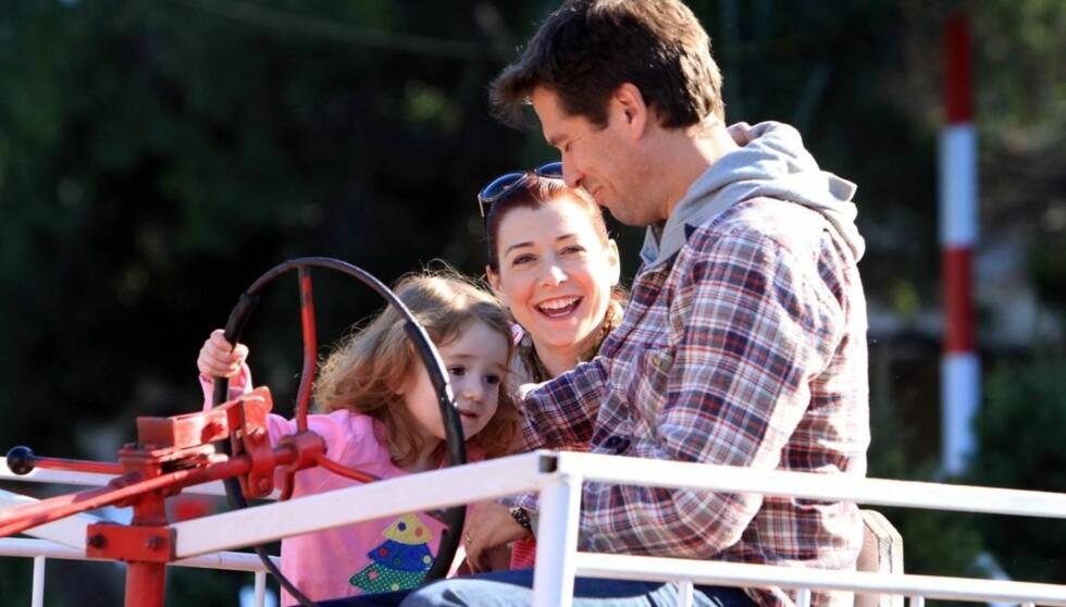 HAPPY FAMILY: Alyson Hannigan og ektemannen Alexis Denisof  så svært lykkelige ut da de nylig var på juletreshopping med datteren Satyana på 2 år. Snart blir hun storesøster. Foto: All Over Press
