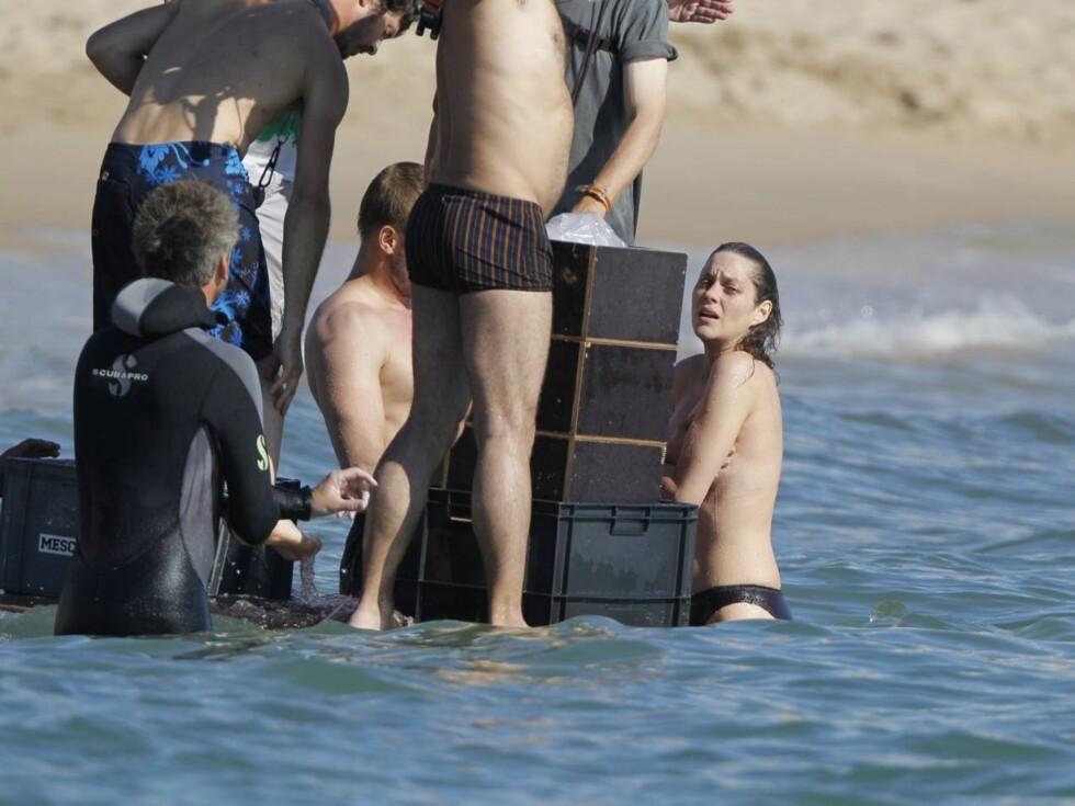 LITE SJENERT:  Marion Cotillard så ikke ut til å bry seg om blikkene fra de mange skuelystne som samlet seg på den offentlige stranden, mens innspillingen pågikk. Foto: Stella Pictures