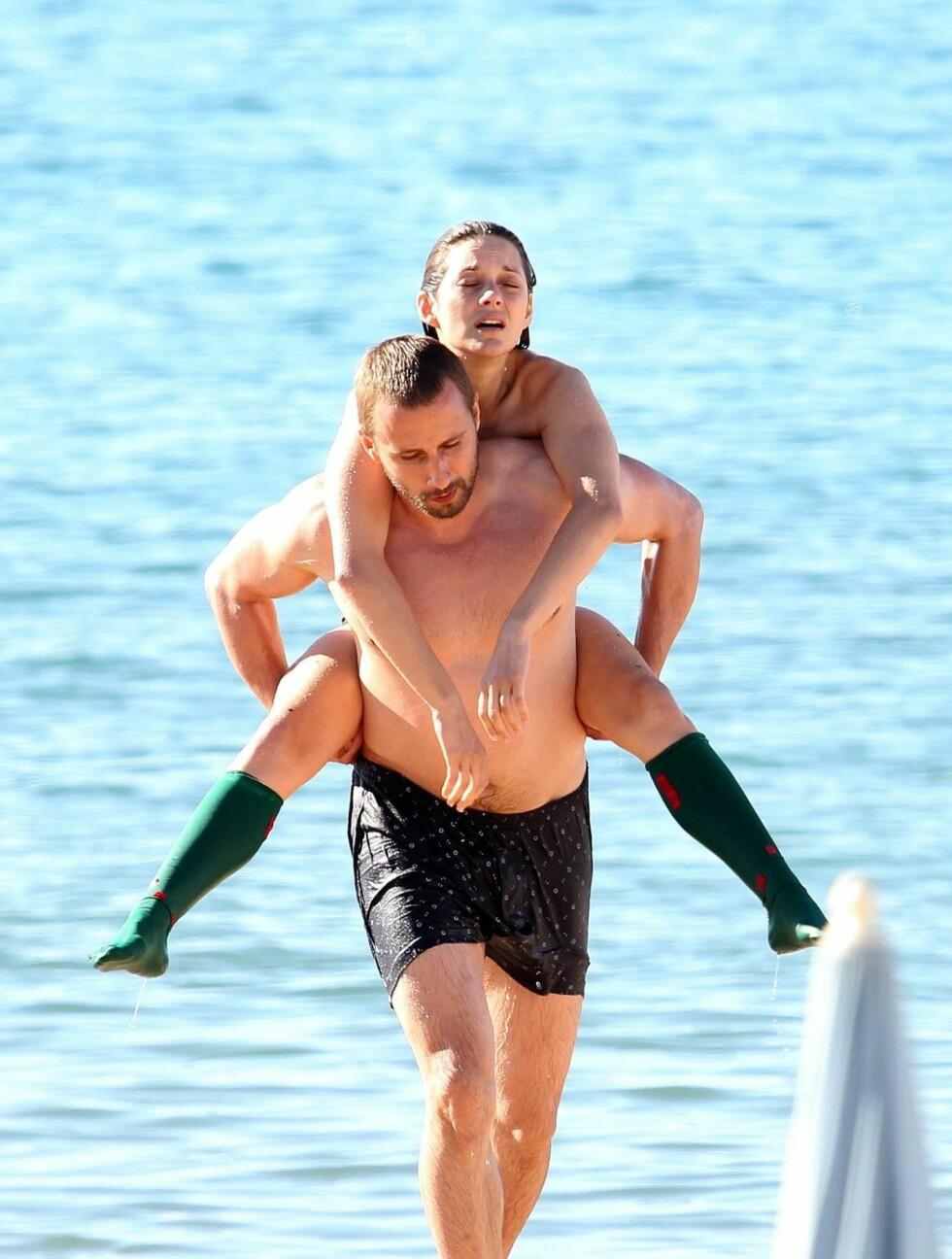 BÅRET I LAND: En mannlig skuespillerkollega bærer Marion i land etter at scenene i det kalde vannet er over. Foto: All Over Press