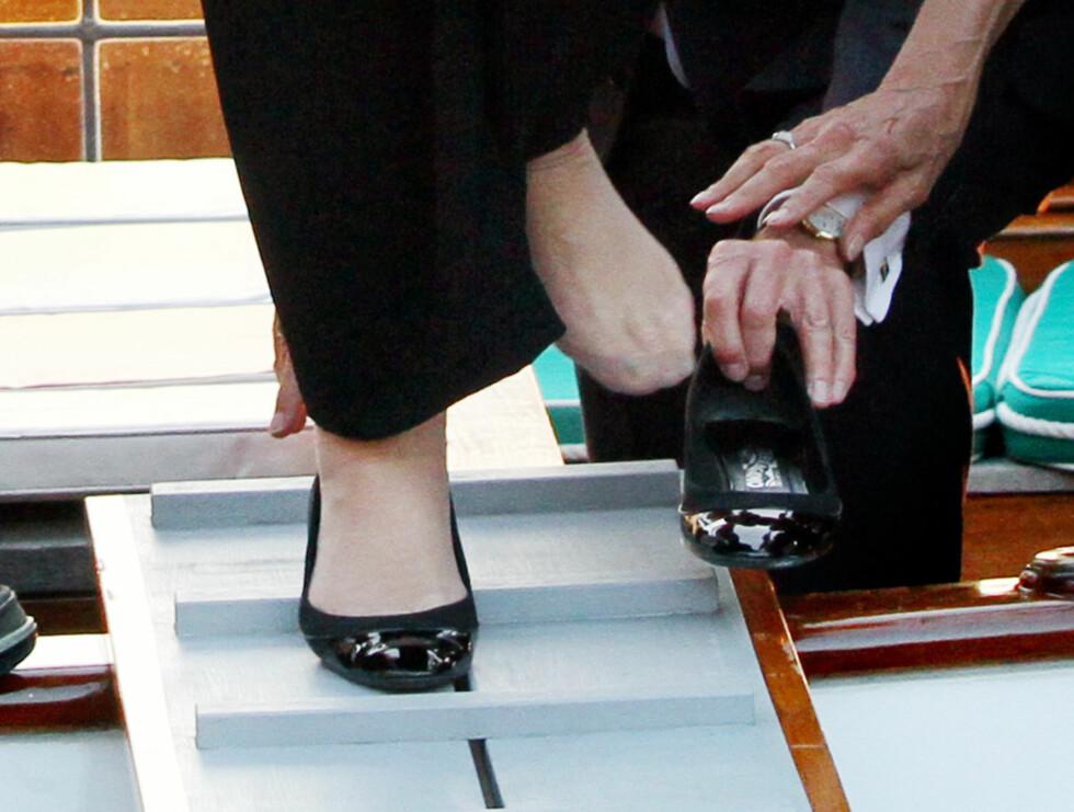 <strong>HJALP TIL:</strong> Til slutt fikk dronningen på seg skoen igjen. Foto: Stella Pictures