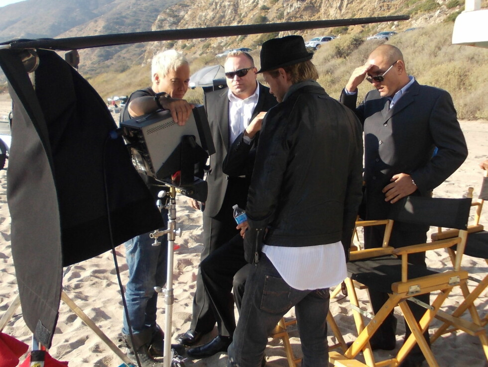 INNSPILLING: Kristian Valen (t.v) sammen med Vinnie Jones (t.h) og Reinert «RayKay» Olsen med ryggen til under innspillingen i Malibu. Foto: Privat