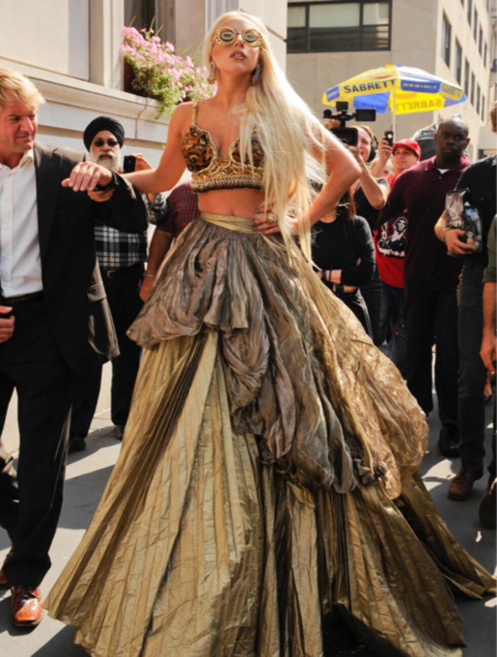 FIKK EN HÅND: Lady Gaga forsøker å posere mens hun støtter seg til en av livvaktene sine. Foto: All Over Press